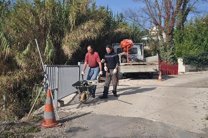 Les employés municipaux terminent les scellements de la barrière