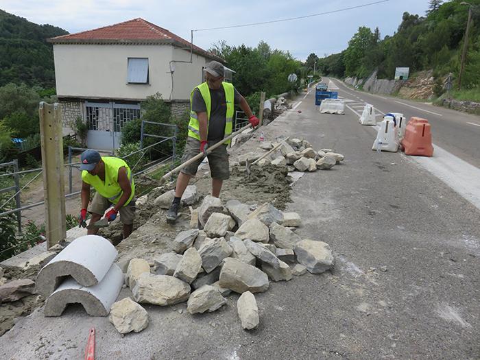 Les maçons construisent un beau mur en pierre
