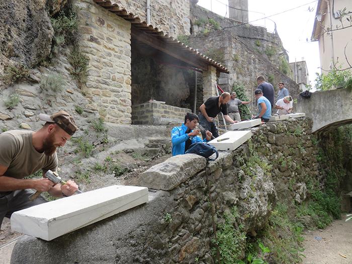 Les stagiaires taillent les pierres qui serviront de margelle au bassin