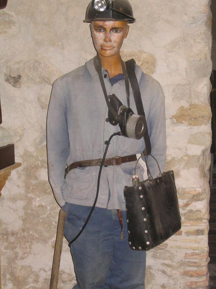 Mineur en tenue : bleu de travail, casque, lampe à batterie, masque ... et cabas pour le casse-croûte